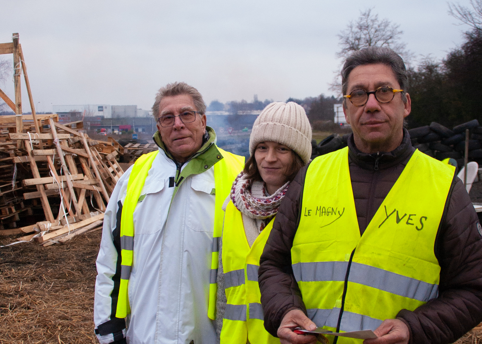 Three people in yellow vests stand and look at the camera
