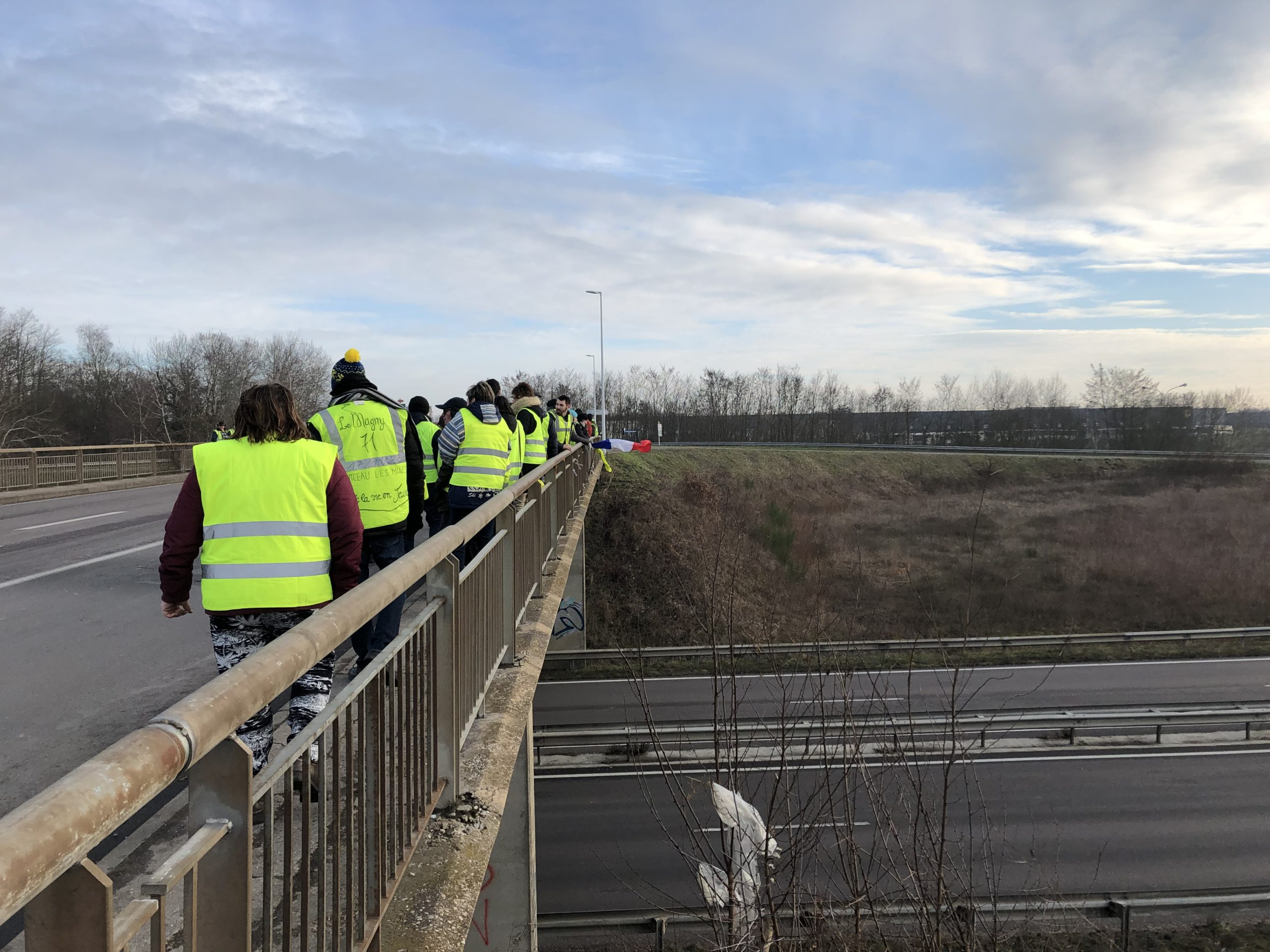 <i>Gilet jaunes</i> on an overpass above a highway